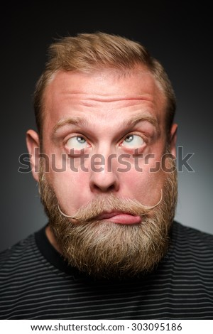 Portrait of fooling bearded man on black. Blond man in black T-shirt making funny faces. - stock photo