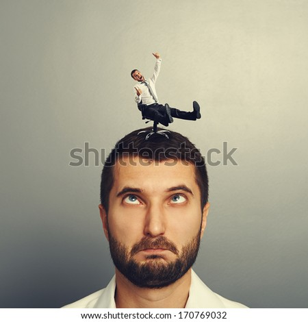 portrait of foolish man with small laughing man on the head - stock photo