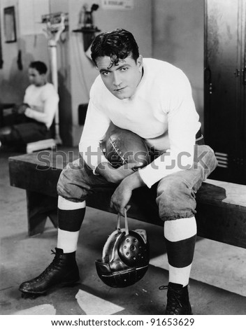 Portrait of football player in locker room - stock photo