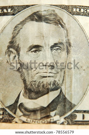 Portrait of former U.S. president Abraham Lincoln as he looks on five dollar bill.