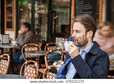 Portrait of forty years old caucasian man in casual outfit drinking coffee in Paris cafe. City lifestyle - relax. - stock photo