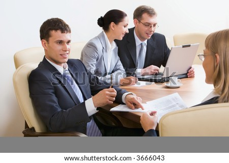 Portrait of four businesspeople discussing different questions sitting in white comfortable chairs at the table with an opened laptop, documents and cup on it - stock photo
