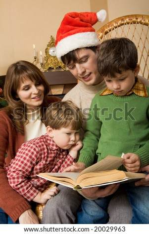 Portrait of four family members looking into book of fairy tales in boy?s hands