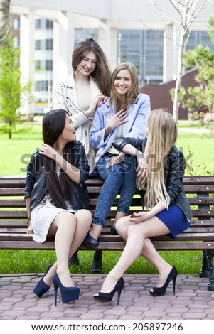 Portrait of four girlfriends in summer park - stock photo
