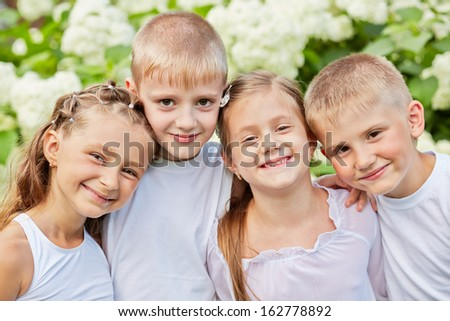 Portrait of four smiling children standing head to head in summer park