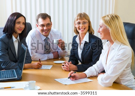 Portrait of four smiling discussing businesspeople sitting around the table with an opened laptop, documents and cups on it - stock photo