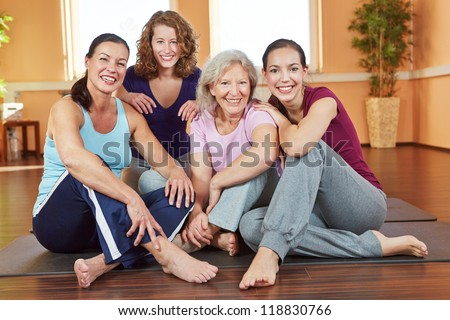 Portrait of four smiling happy women sitting in a fitness center - stock photo