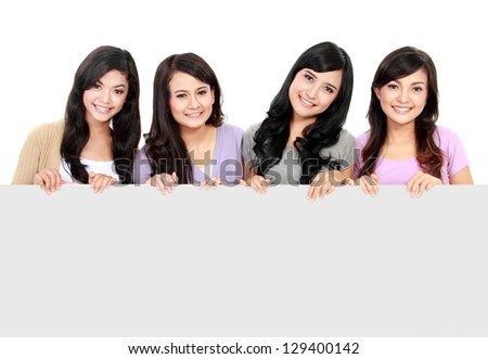 portrait of four teenage girls standing and holding a white board
