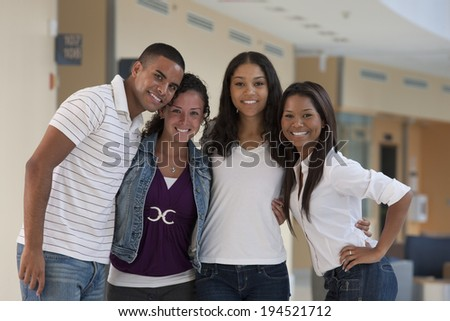 Portrait of four university students smiling in a group