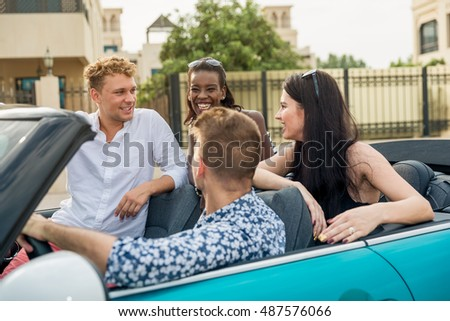 Portrait of four young friends sitting in blue cabriolet  on the sea shore have fun and laughing. Guys are looking for each other.