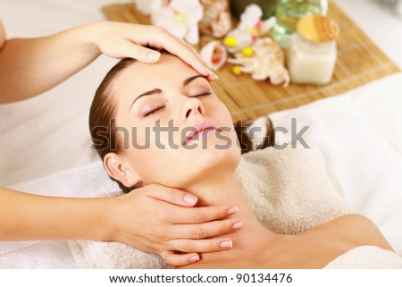 Portrait of fresh and beautiful brunette woman taking head massage , isolated on white background - stock photo