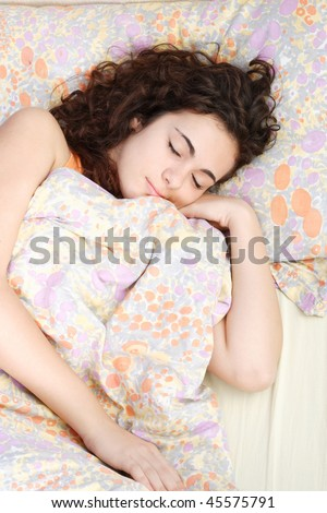 Portrait of fresh and beautiful teen woman on bed - stock photo