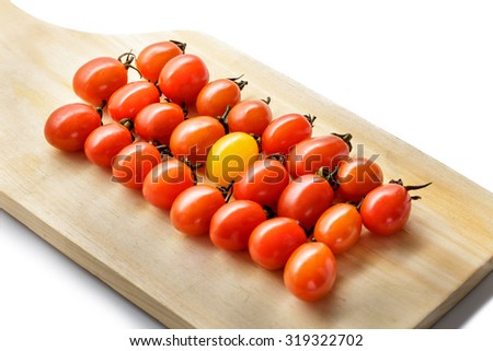 portrait of fresh cherry tomatoes on a wooden cutting board isolated on white background - stock photo