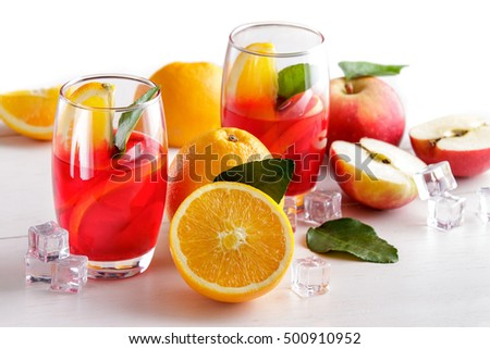 portrait of fresh mix syrup with orange, apple slice and ice cube isolated on white background