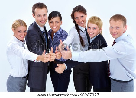 Portrait of friendly business team showing thumbs up and looking at camera