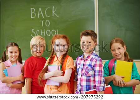 Portrait of friendly classmates with books looking at camera on background of blackboard - stock photo