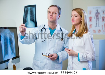 Portrait of friendly confident doctors in hospital looking at x-ray. Enthusiastic medical staff at work. Female and male doctors in diagnostics room.  - stock photo