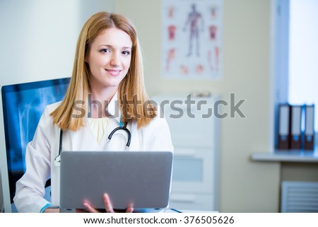 Portrait of friendly confident female doctor in hospital working on laptop. Enthusiastic medical staff at work. Female doctor in diagnostics room.  - stock photo