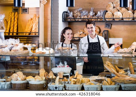 Portrait of friendly couple at bakery display with pastry - stock photo