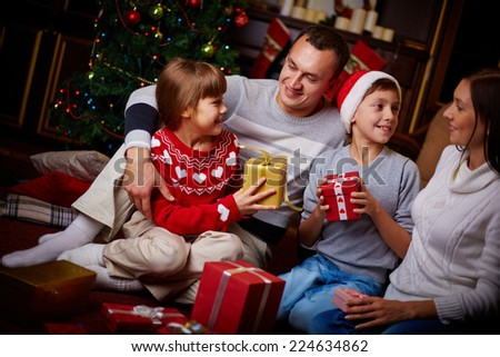 Portrait of friendly family with gifts spending Christmas evening at home - stock photo
