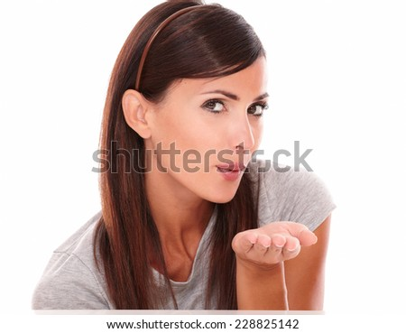 Portrait of friendly girl blowing a kiss forward and looking at camera on isolated studio - stock photo