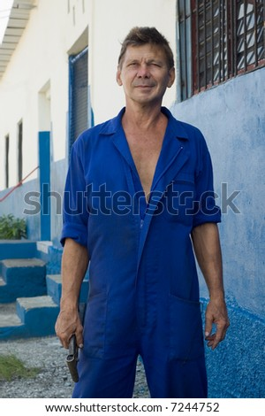 Portrait of friendly mature worker with tool in a hand - stock photo