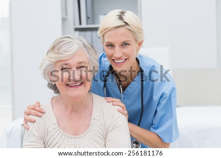 Portrait of friendly nurse with hands on senior patients shoulders in clinic - stock photo