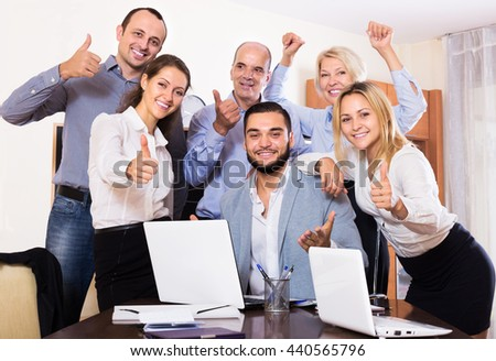 Portrait of friendly relaxed employees sitting at desk