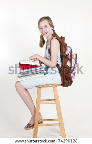 Portrait of friendly school girl student with backpack, sitting on a stool, holding notebooks and reading - stock photo