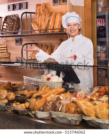 Portrait of friendly senior woman at bakery display with a pastry