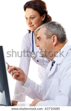 Portrait of friendly therapists looking at computer monitor where senior man pointing - stock photo