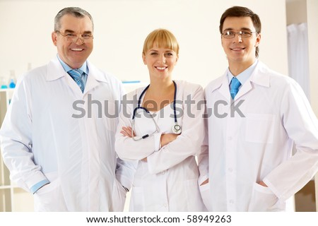 Portrait of friendly therapists standing in line and looking at camera with smiles