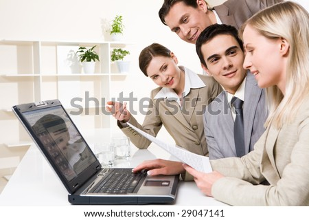 Portrait of friendly workteam looking at confident businesswoman with document in hand typing on laptop