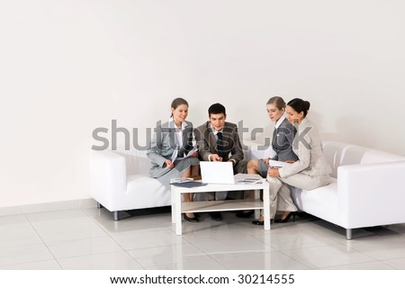 Portrait of friendly workteam looking at laptop monitor being pointed at by smart employer - stock photo