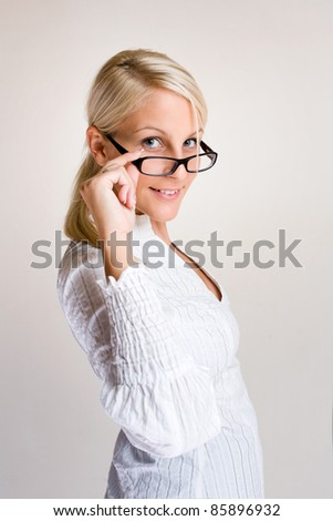 Portrait of friendly young business woman peeking over glasses. - stock photo