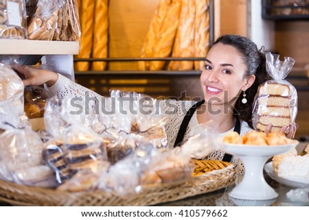 Portrait of friendly young woman at bakery display with american pastry - stock photo