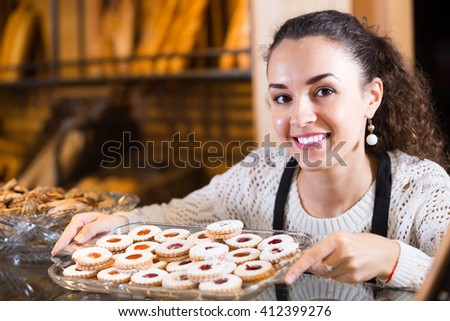 Portrait of friendly young woman at bakery display with european pastry - stock photo
