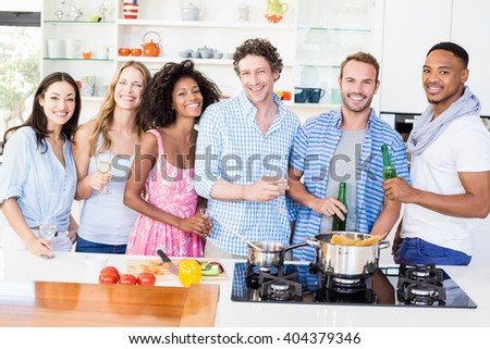 Portrait of friends standing together and holding beer bottles and glasses of wine in kitchen - stock photo