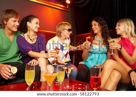 Portrait of friends with cocktails sitting on the sofa in the nightclub
