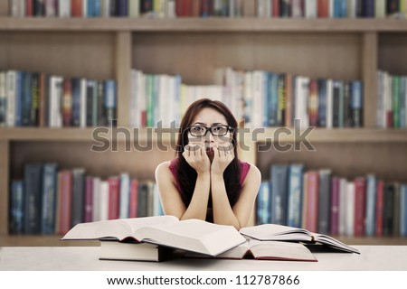 Portrait of frightened female college student with textbooks biting her nails. shot in the library - stock photo
