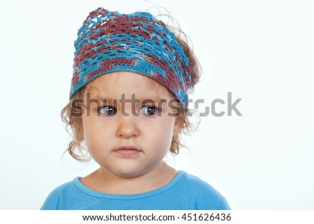 Portrait of frightened little girl in blue handmade headband looking away.Isolated. - stock photo
