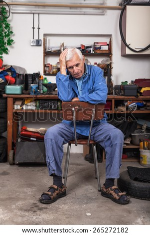 Portrait of frustrated senior worker sitting on the chair in his workshop. - stock photo