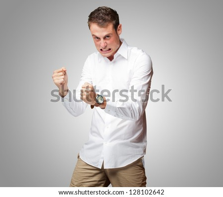 Portrait Of  Frustrated Young Man On Gray Background - stock photo