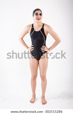 portrait of full body young asian female swimmer in blue swimsuit with goggle and swimming hat. laugh posing in studio set white background - stock photo