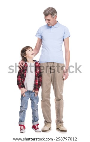 Portrait of full length of grandfather and grandson are standing on white background and looking at each other.