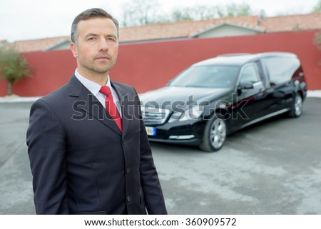 Portrait of funeral director in front of hearse - stock photo
