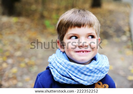 Portrait of funny adorable and fashionable little boy with big blue eyes in blue coat and scarf outdoor at the nice autumn day - stock photo