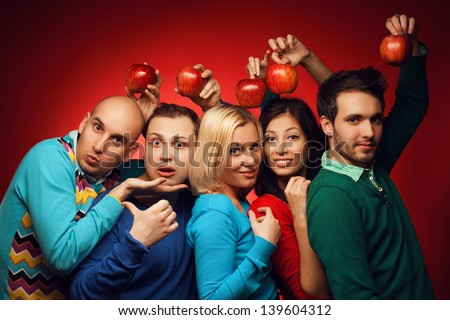 Portrait of funny and confused students (close friends) posing over red background and holding red apples above heads. Education (health-care) concept. Hipster style. Studio shot