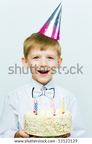 Portrait of funny child with cap and cake at his birthday - stock photo