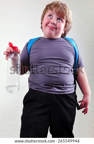 portrait of funny cute blond schoolboy with a bottle of water making faces - stock photo